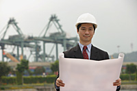 Engineer with plans and hard helmet looking at camera - Asia Images Group