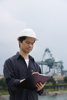 Man with hard helmet writing on clipboard - Asia Images Group