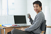 Man with cup relaxing at desk and looking at camera - Asia Images Group