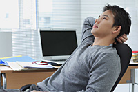Man leaning back in office chair - Asia Images Group