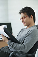 Man in office chair writing on clipboard - Asia Images Group