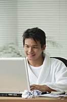 Man in bathrobe working at computer - Asia Images Group