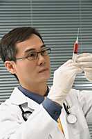 Doctor preparing hypodermic needle - Asia Images Group