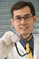 Doctor with stethoscope smiling at camera - Asia Images Group