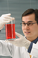 Scientist examining container of fluid - Asia Images Group