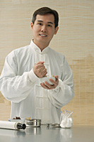 Doctor experimenting with traditional Chinese medicine - Asia Images Group
