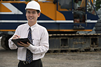 Man with hard helmet and clipboard looking at camera - Asia Images Group