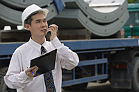 Man with hard helmet speaking into walkie talkie - Asia Images Group
