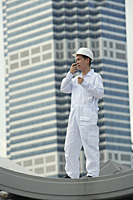 Man with walkie talkie giving directions - Asia Images Group