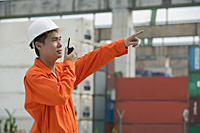 Construction worker giving directions on walkie talkie - Asia Images Group