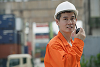 Construction worker talking on walkie talkie - Asia Images Group