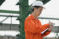 Construction worker making notes on clipboard - Asia Images Group