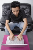 Young man sitting on couch using laptop - Asia Images Group