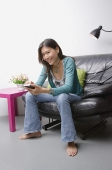Young woman sitting on couch using organizer - Asia Images Group