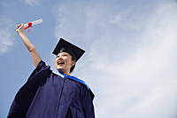 University student in graduation robe cheering - Asia Images Group