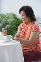 Mature woman having tea and listening to music - Asia Images Group