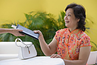 Mature woman in restaurant being handed bill - Asia Images Group