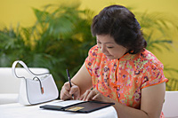 Mature woman in restaurant paying bill - Asia Images Group