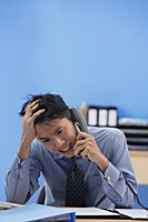 Businessman talking on the phone being frustrated - Asia Images Group