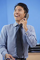 Businessman laughing while on the phone - Asia Images Group