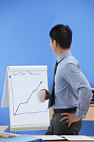 Businessman looking at statistics - Asia Images Group