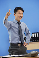 Businessman giving thumbs up at camera - Asia Images Group