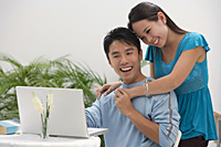 Young woman leaning on shoulder of man at the computer - Asia Images Group