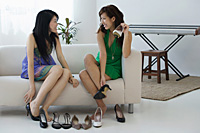 Young women sitting on sofa trying on shoes - Asia Images Group