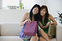 Young women sitting on sofa with shopping bags - Asia Images Group