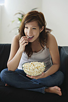 Young woman eating popcorn on sofa - Asia Images Group