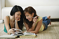 Young women lying on the floor reading book - Asia Images Group