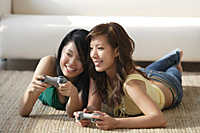 Young women lying on the floor, playing video games - Asia Images Group
