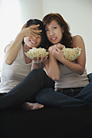 Young women enjoying popcorn - Asia Images Group