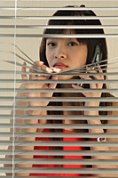 Young woman behind Venetian blinds - Asia Images Group