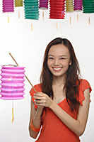 Young woman with Chinese lantern smiling at camera - Asia Images Group