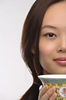 Young woman with traditional tea cup looking at camera - Asia Images Group