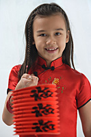 Young girl in traditional Chinese dress holding red lantern and looking at camera - Asia Images Group