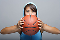 Young woman with basketball looking up - Asia Images Group