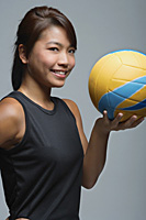Young woman with volleyball smiling at camera - Asia Images Group