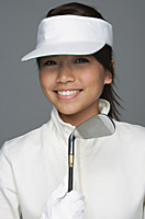 Young woman in golfing outfit looking at camera - Asia Images Group