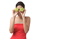 Young woman holding two apples over eyes - Asia Images Group