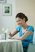 Young woman sitting in restaurant - Asia Images Group