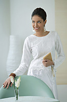 Young woman smiling with hand on chair - Asia Images Group