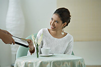 Young woman sitting in restaurant, being handed a menu - Asia Images Group
