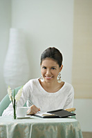 Young woman sitting in restaurant, signing bill - Asia Images Group
