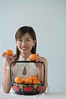 Young woman with fruit smiling at camera - Asia Images Group