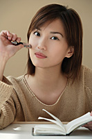 Young woman with journal looking at camera - Asia Images Group