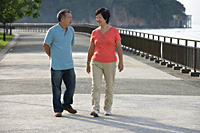 Couple strolling along the waterfront - Asia Images Group