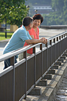 Couple having a conversation while leaning in fence - Asia Images Group