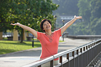 Woman with arms outstretched looking into distance - Asia Images Group